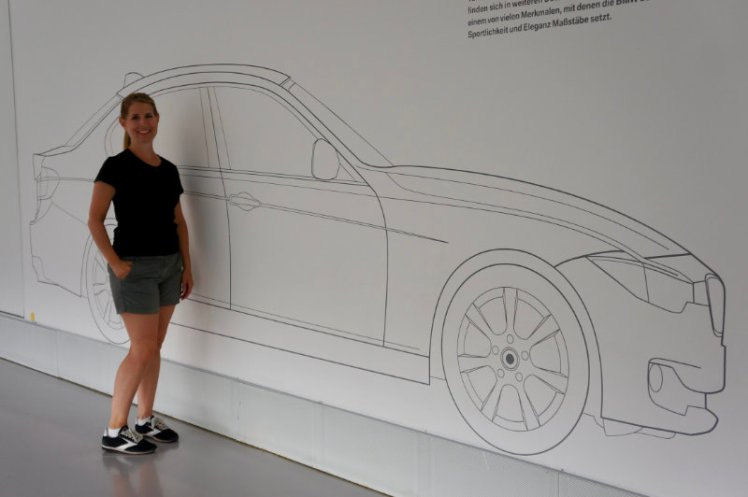 Jen in front of a line drawing of a 3-series.